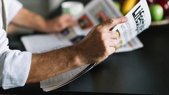 Man's hand holding newspaper