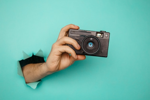 Man's hand holding old camera from blue torn paper