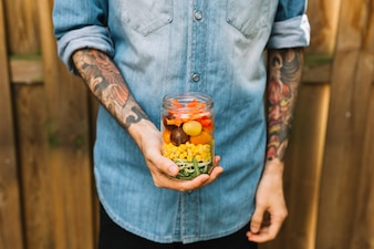 Man's hand holding open jar with pasta salad