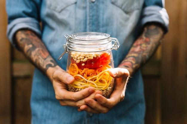 Man's hand holding pasta salad
