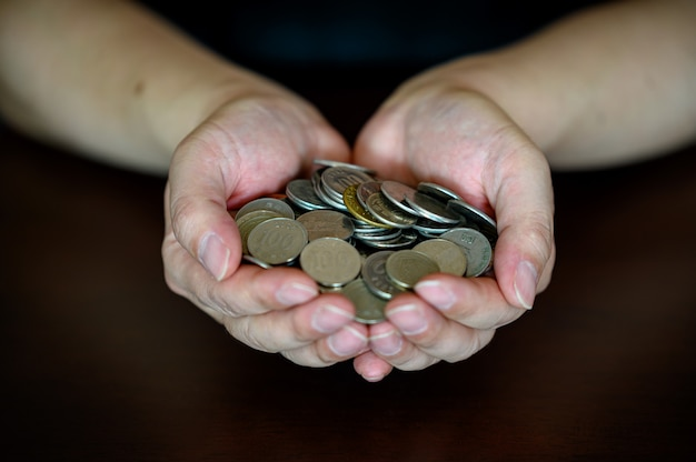 A man's hand holding a pile of coins on a wooden table.