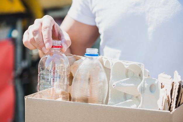Man's hand holding plastic bottles and egg carton in cardboard box