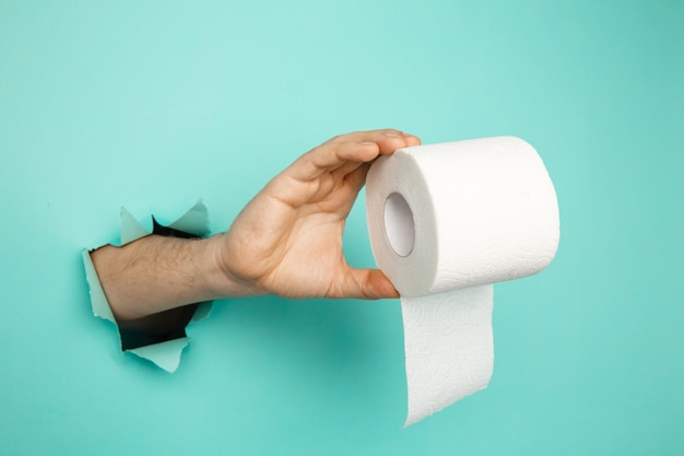 Man's hand holding a roll of toilet paper from blue torn background