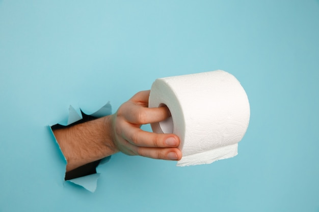 Man's hand holding a roll of toilet paper from blue torn paper.