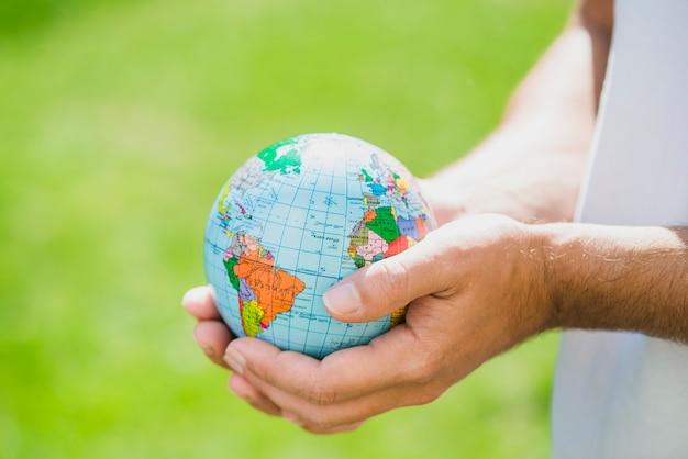 Man's hand holding small globe
