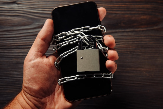 Man's hand holding a smartphone with padlock. concept of smartphone protection against malware, antivirus