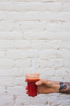 A man's hand holding smoothie in plastic disposable cup with straw against wall