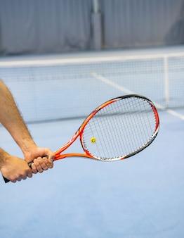 Man's hand holding tennis racket on tennis court