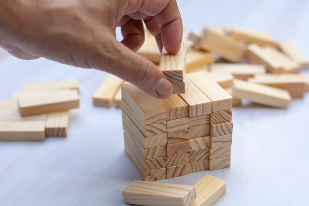 Man's hand holding a top of wooden blocks over wooden block