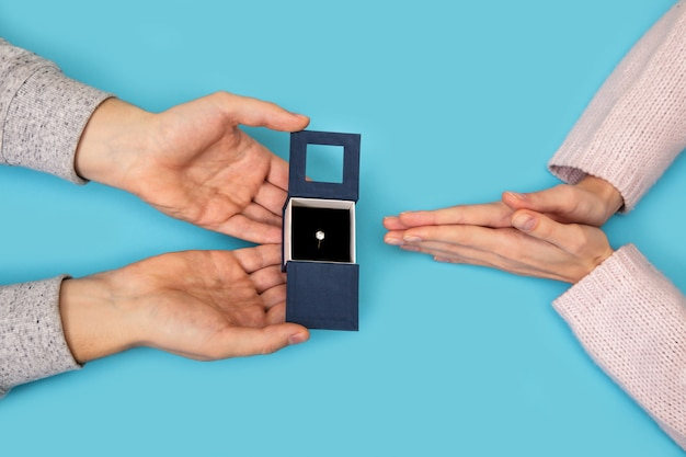 青の女性の手のための結婚指輪ボックスを持っている男の手