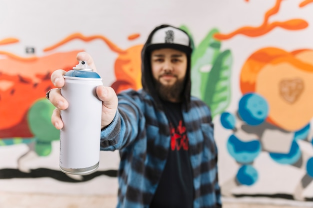 Man's hand holding white aerosol can