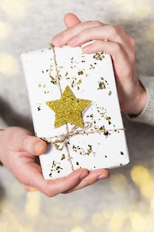 Man's hand holding white gift box with golden star, christmas present