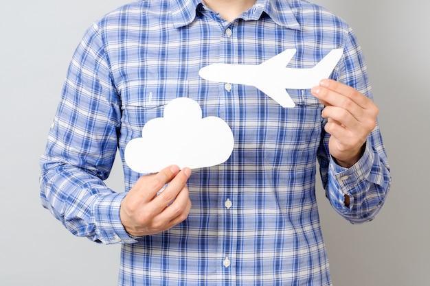 Рука человека держит белую модель самолета и облака