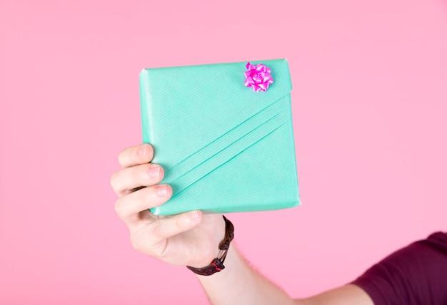 人の手はピンクの背景に包まれたターコイズギフトボックスを包んで