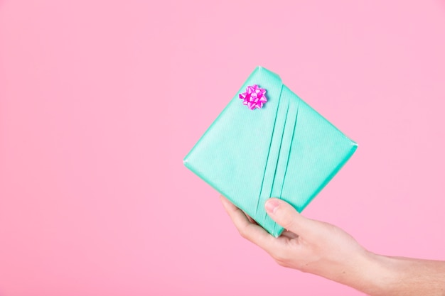 Man's hand holding wrapped turquoise present box on pink background
