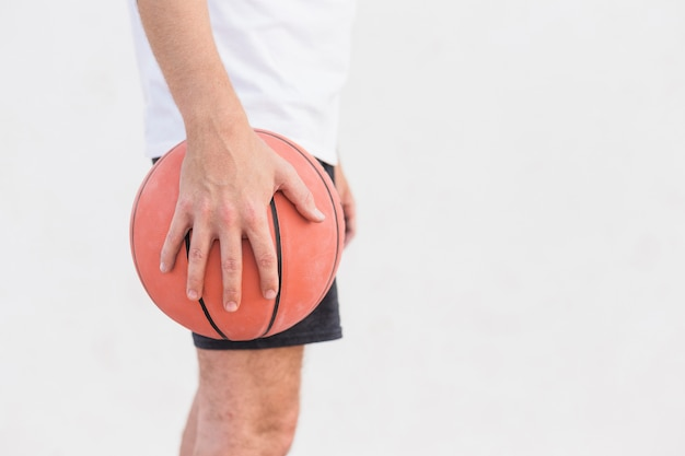 Man's hand holdng basketball