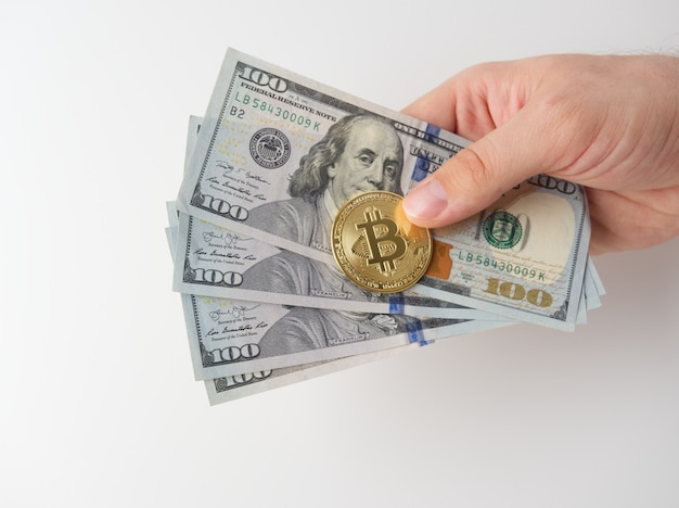 A man's hand holds 100 dollar bills and a golden bitcoin. white background. the concept of mining and mining of cryptocurrency