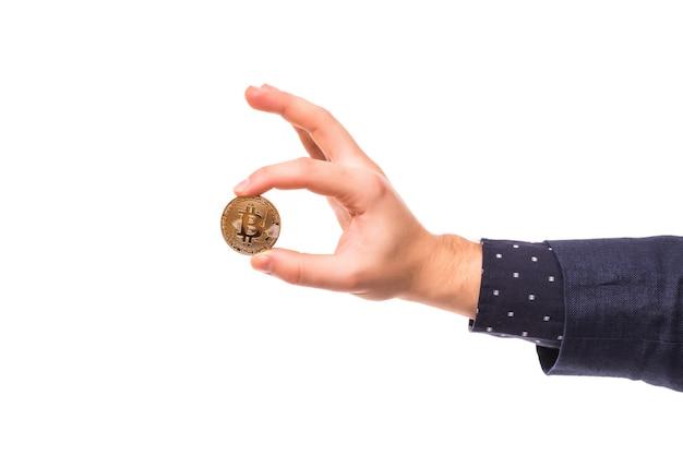 Рука человека держит золотой биткойн