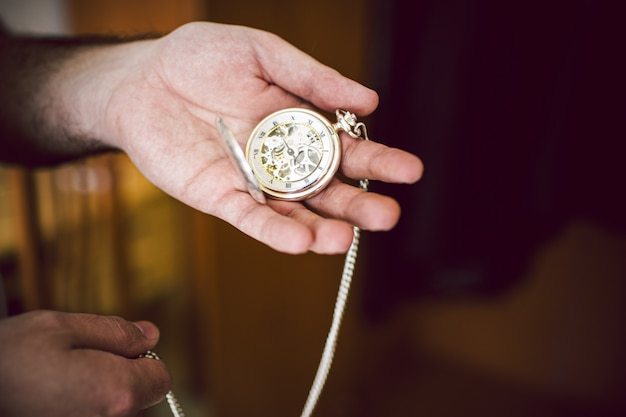 A man's hand holds an antique pocket watch with its gears and hand in sight.
