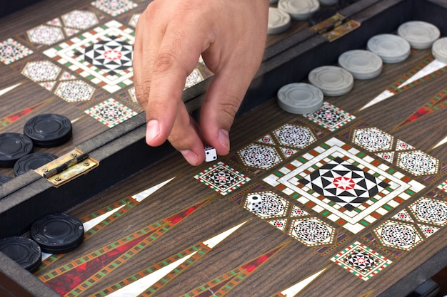 A man's hand holds a backgammon game