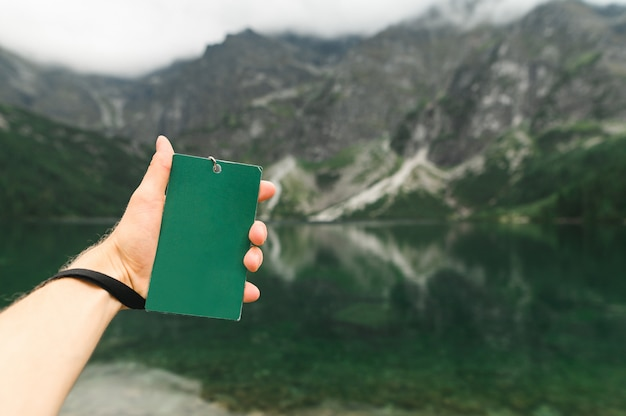 Man's hand holds a blank green turgid against the background of lake morskie oko. copy space. empty space
