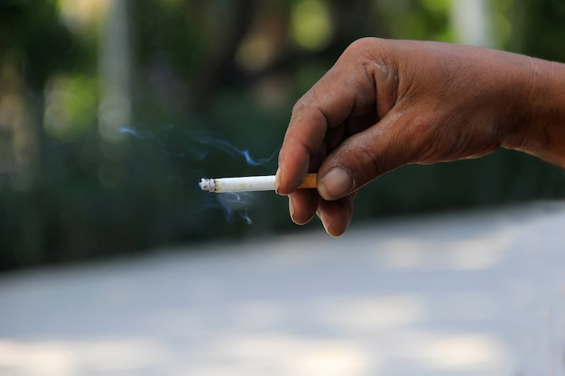 A man's hand holds a cigarette that is burning