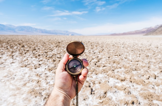 A man's hand holds a compass in the middle of the death valley desert in california usa