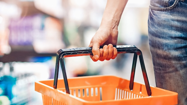 Man's hand holds an empty basket in the supermarket. grocery shopping concept