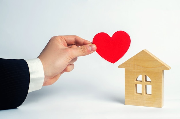 The man's hand holds the heart and the house