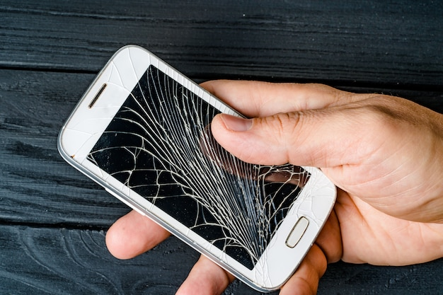 Man's hand holds mobile phone with broken touchscreen on dark background