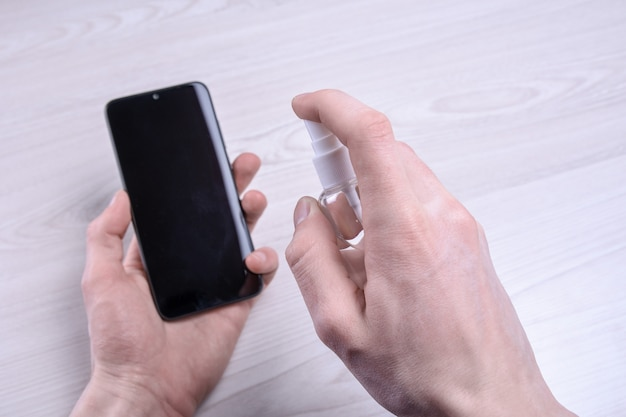 A man's hand holds and snaps a disinfectant spray and disinfect the phone to disinfect various surfaces that people touch.antibacterial antiseptic gel for hands