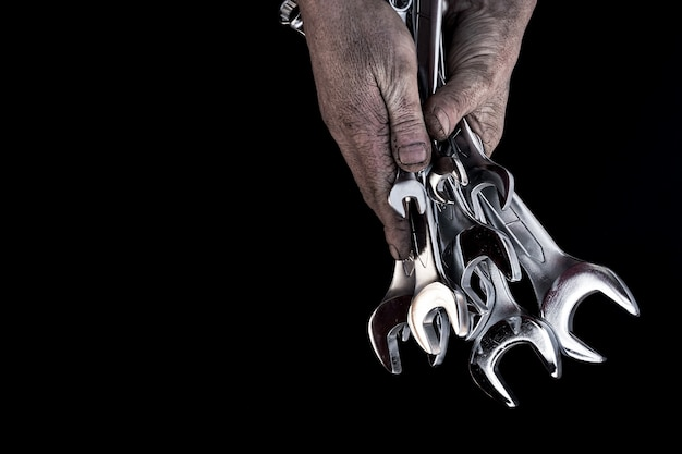 Man's hand holds steel wrenches on black background.