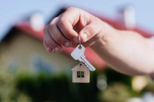 Рука человека держит ключи от дома на фоне жилых домов.