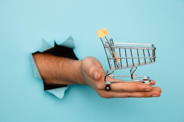남자의 손을 구멍을 통해 파란색 종이 배경에 미니 식료품 쇼핑 트롤리를 보유합니다. 판매 개념.