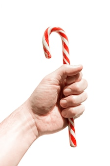 Man's hand holds traditional christmas striped candy cane