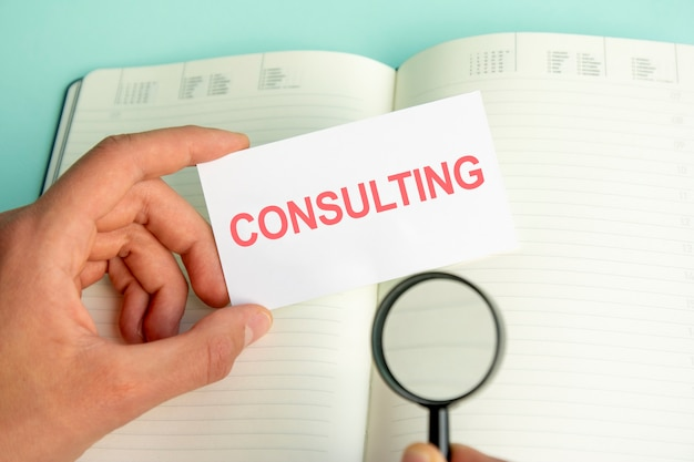 A man's hand holds a white card with the text consulting above an open paper notebook and a magnifying glass in a black frame, business concept