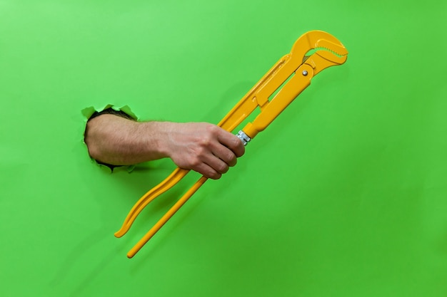 A man's hand holds a yellow tube key through a torn green paper. hand through torn green paper. photo with place for your text, logo and design. concept repair and tool