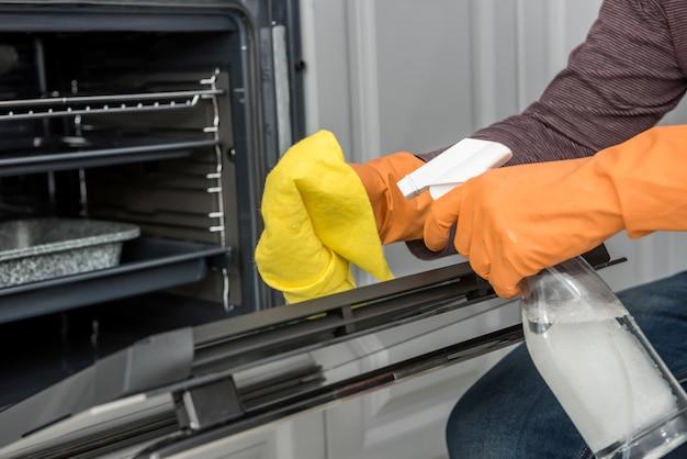 台所のオーブンを掃除する手袋をはめた男の手。家事