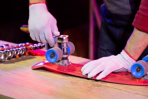 赤いプラスチック製の子供スケートボードを固定する作業用手袋の男の手