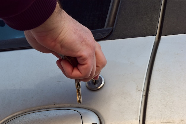 A man's hand inserts a key into the keyhole of a used car door. there are several keys in hand.