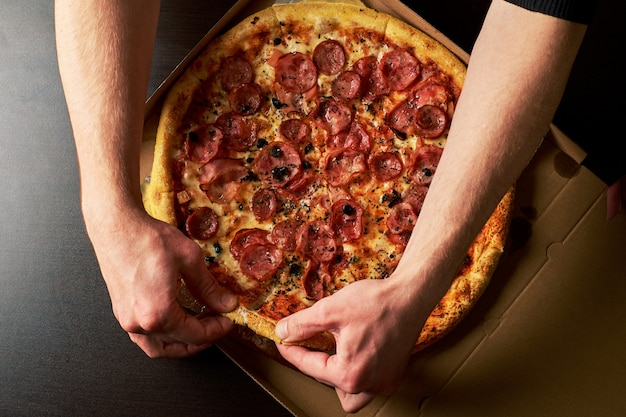 Man's hand is holding slice cheese pizza from whole pizza in a cardboard box dark table background.