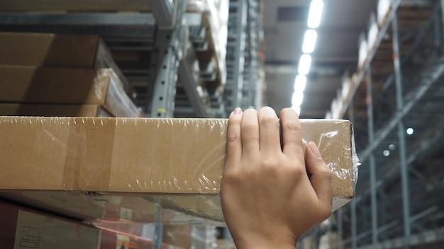 人間の手が倉庫の大規模な保管場所で箱を拾ったり、配送のために貨物を受け取ったりしています。