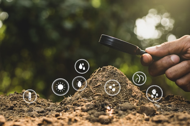 A man's hand is using a magnifying glass to shine the manure with the technology icons around