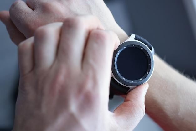 На руке мужчины черные умные часы
