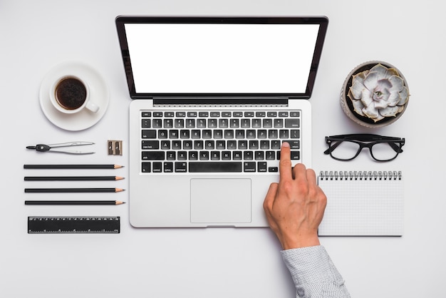 Man's hand on laptop keypad over desk with arranged office stationeries