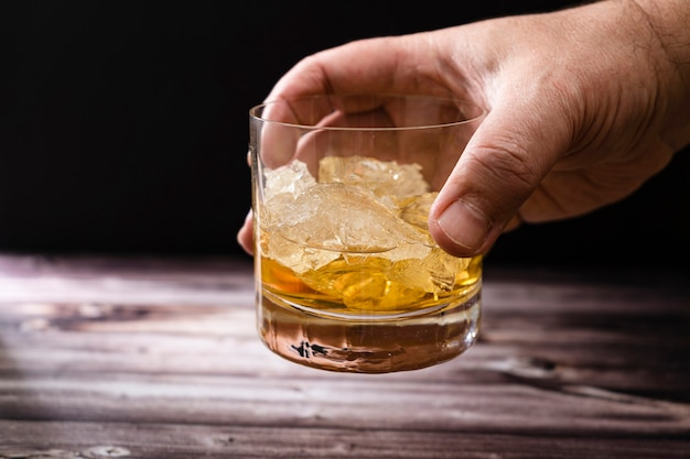 A man's hand lifting a glass with whiskey or scotch and large chunks of ice from a rustic wooden table
