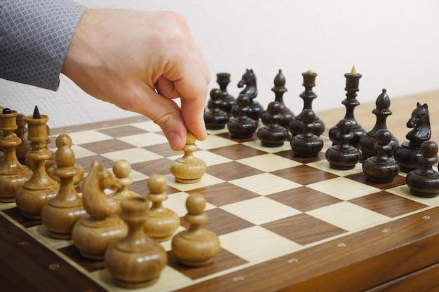 チェスゲームで最初の動きをする男の手。 e2-e4移動。ホワイトがゲームを開始します。