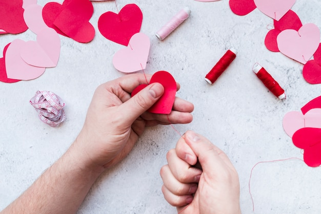 Man's hand making the red and pink paper heart shape garland with thread on white background