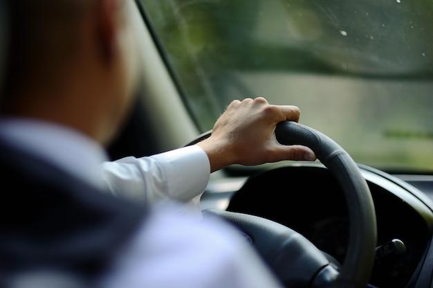 車のハンドルに男の手