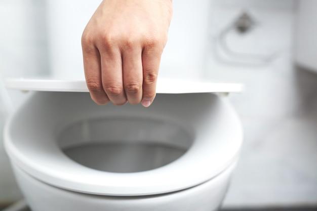 Рука человека открывает крышку унитаза